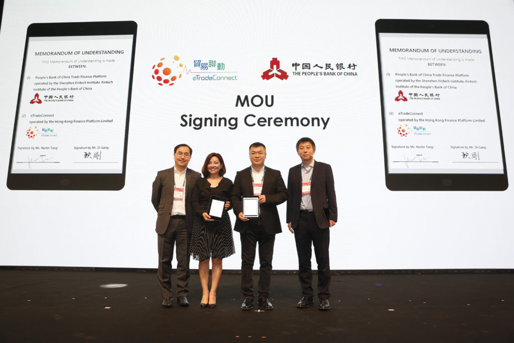 Ms Haster Tang, Chief Executive Officer of the Hong Kong Trade Finance Platform Company Limited (second from left), and Mr Di Gang, Deputy Director-General of the Institute of Digital Currency of the People's Bank of China and Director of Shenzhen Fintech Institute (second from right), sign the Memorandum of Understanding to conduct a Proof-of-Concept trial. The signing ceremony is witnessed by Mr Colin Pou, Executive Director (Financial Infrastructure) of the HKMA (first from left), and Mr Mu Changchun, Director-General of the Institute of Digital Currency of the People's Bank of China (first from right), November, 2019
